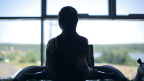 Silhouette of girl running on the treadmill and looking into the large window stock video