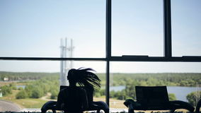 Silhouette of girl running on the treadmill and looking into the large window. Left to right dolly shot stock video footage