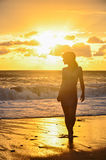 Silhouette of girl  in sea. Silhouette of girl in frock standing in sea at golden sunset background Stock Image