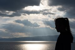 Silhouette of a girl on the shore of Lake Ohrid royalty free stock photo