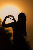 Silhouette of a girl showing heart. With fingers Royalty Free Stock Image