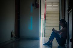 Silhouette of girl sitting alone,Sad and Serious women sitting hug his knee alone of close condo., Dramatic moment. with copy. A Silhouette of girl sitting alone stock image