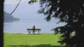 Bench With Breathtaking View. Silhouette of a girl sitting on a bench and enjoying breathtaking peaceful landscape. Alone woman on chair sightseeing mountain stock video