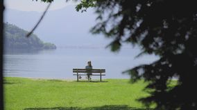 Bench with breathtaking view. Silhouette of a girl sitting on a bench and enjoying breathtaking peaceful landscape. Alone woman on chair sightseeing mountain stock video footage
