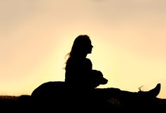Silhouette of Girl Sitting OUtside with Large Dog Stock Photography