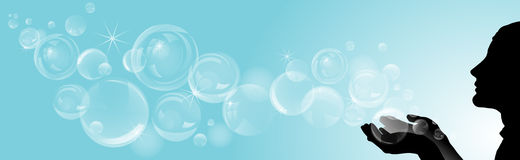 Silhouette of girl with soap bubbles on blue background. Royalty Free Stock Image
