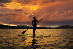 Silhouette of a girl on Stand Up Paddle Board. On the background of stormy sky. SUP Royalty Free Stock Photo