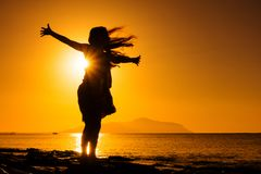 Silhouette of girl standing at the beach against sunrise. Silhouette of happy girl standing at the beach against sunrise Royalty Free Stock Image