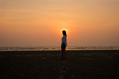 Silhouette girl standing on beach and sunset. Royalty Free Stock Photo