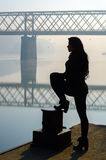 Silhouette of girl standing on dock with bridge in background Stock Images