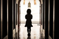Silhouette of a girl standing pay respect. The silhouette of a girl standing pay respect in a temple Royalty Free Stock Images