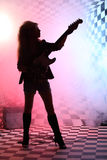 Silhouette of girl standing and playing electric guitar. In studio in smoke and pink light Stock Photos