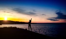 Silhouette girl at river. Silhouette of a girl standing at seaside at sunset Stock Images