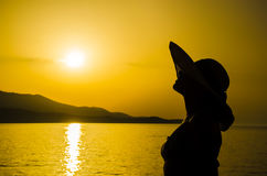 Silhouette girl with straw hat on the beach Stock Photo