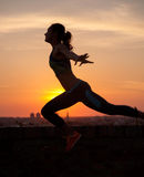 Silhouette of Girl streching at Sunrise or Sunset Stock Photo