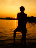 Silhouette of a girl in the sunset. Girl silhouette on sunset beach background Stock Photo