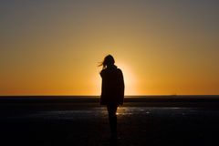 Silhouette of a girl at sunset. Silhouette of a girl on the beach at sunset Royalty Free Stock Images