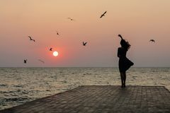 Silhouette of a girl on a sunset background sunrise on the sea stock photography
