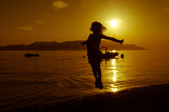 Silhouette of girl at sunset Stock Photos