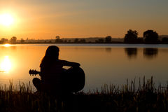 Silhouette of a girl at sunset playing the guitar Stock Images
