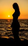 Silhouette of a girl at sunset profile position Royalty Free Stock Photo