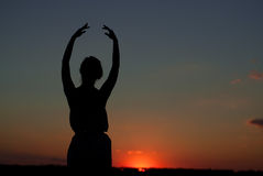 Silhouette of a girl at sunset. In summer Stock Photos