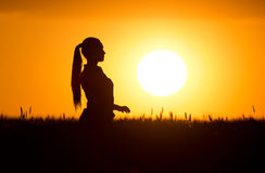 Silhouette of girl at sunset Stock Images