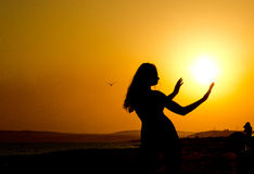 Silhouette of a girl with thin waist and hands outstretched to the sun at sunset Stock Photography