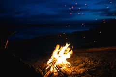 The silhouette of girl tourist around the campfire at night on the river shore Stock Image