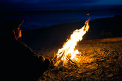 The silhouette of girl tourist around the campfire at night on the river shore Stock Photo