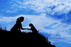 Silhouette of girl train a dog. Silhouette of siting girl train a dog Royalty Free Stock Photo