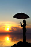 Silhouette of a girl with an umbrella in the sunset Royalty Free Stock Photos