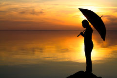 Silhouette of a girl with an umbrella in the sunset Royalty Free Stock Photography