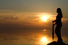 Silhouette of a girl with an umbrella in the sunset Royalty Free Stock Image