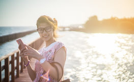 Silhouette Girl using smartphone at the beach Stock Photography