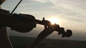 Silhouette girl violinist playing the violin at sunset sky background. stock video footage