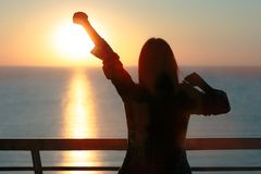 Silhouette of a girl waking up stretching arms in morning sunrise light Stock Image