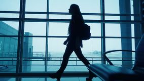 Silhouette of girl walking on airport terminal. Silhouette of young girl walking on window of airport terminal with small backpack, slow motion stock footage