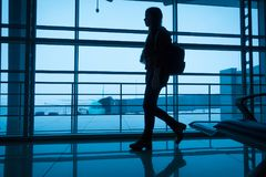 Silhouette of girl walking on airport terminal. Silhouette of young girl walking on window of airport terminal with small backpack, blue toned image Stock Photography