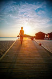 Silhouette of a girl walking along the pier at sunset Royalty Free Stock Photo