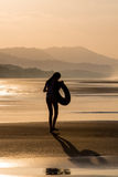 Silhouette of a girl walking on the beach Stock Photos