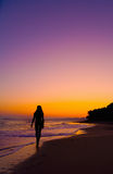 Silhouette of girl walking on a beach at sunset Stock Photos