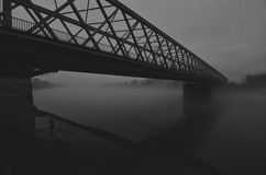 Silhouette of the girl walking under bridge on misty winter day stock images
