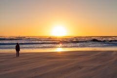 Silhouette girl watching a sunset on a sandy beach with rough oc. Ean wind. Photo taken in Cape Town Stock Image