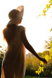 Silhouette girl in a white dressin a white hat looks at the sunset on a green glade Royalty Free Stock Images
