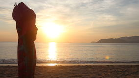 Silhouette of girl who admires scenery of sunrise above sea stock video