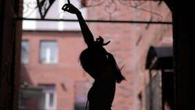 Silhouette of a girl who dances and has fun on the street. unrestrained fun outdoor. Silhouette of a girl who dances and has fun on the street. unrestrained fun stock footage
