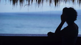 Silhouette of a girl who looks into the distance against the blue ocean. Young woman admires the resort`s tropical. Scenery and straightens her hair. Rest stock footage