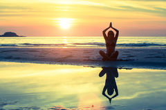 Silhouette of girl in yoga pose sitting on the beach. During sunset Stock Photo