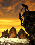 Silhouette of girls climbing on the rock. Royalty Free Stock Images